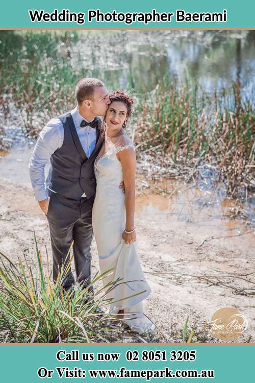 Photo of the Groom kiss the Bride near the lake Baerami NSW 2333