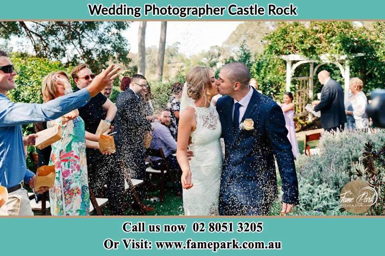 Photo of the Bride and the Groom kissing while showering rice by the visitors Castle Rock NSW 2333