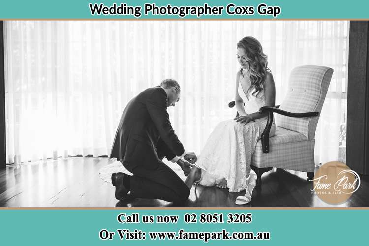 The Bride is being helped by the Groom trying to put on her shoes Coxs Gap NSW 2333