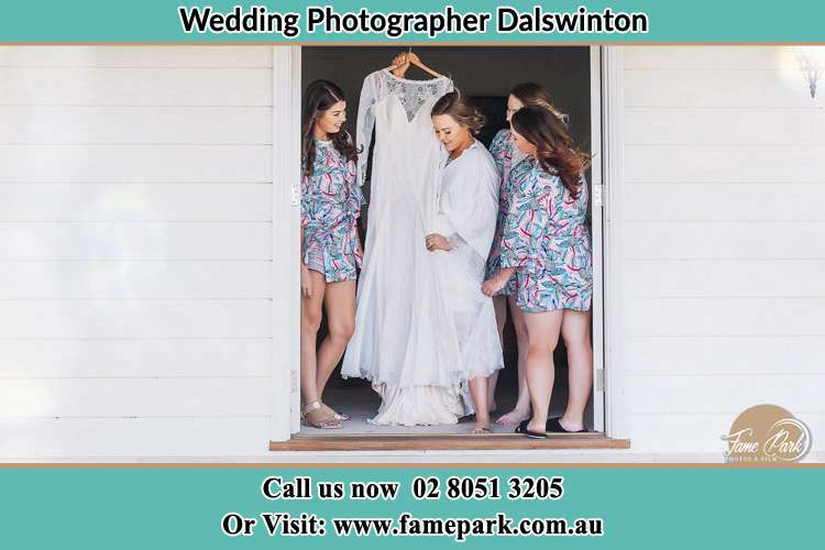 Photo of the Bride and the bridesmaids checking the wedding gown at the front door Dalswinton NSW 2328