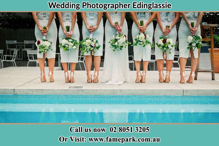 Behind photo of the Bride and the bridesmaids holding flowers near the pool Edinglassie NSW 2333