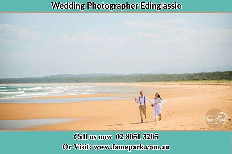 Photo of the Groom and the Bride walking at the sea shore Edinglassie NSW 2333
