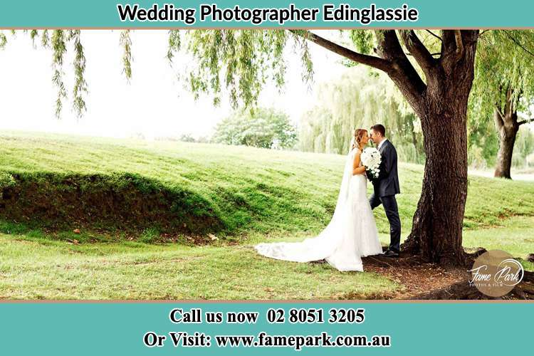 Photo of the Bride and the Groom kissing under the tree Edinglassie NSW 2333
