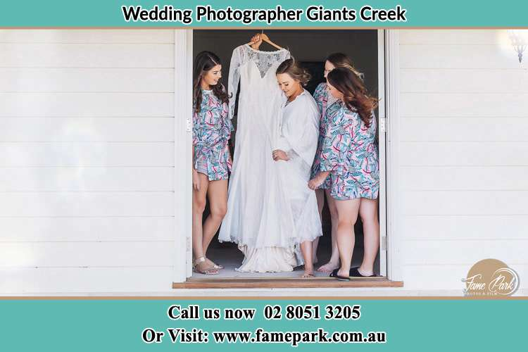 Photo of the Bride and the bridesmaids checking the wedding gown at the front door Giants Creek NSW 2328