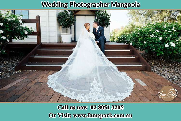 Photo of the Bride and the Groom looking each other while sitting at the staircase Mangoola NSW 2333