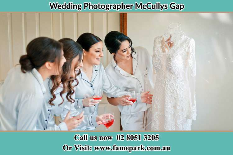 Photo of the Bride and the bridesmaids looking on the wedding gown McCullys Gap NSW 2333