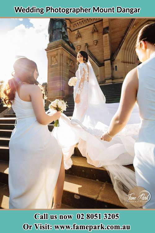 Photo of the Bride smiling on the bridesmaid holding the tail of her wedding gown at the front of the church Mount Dangar NSW 2333