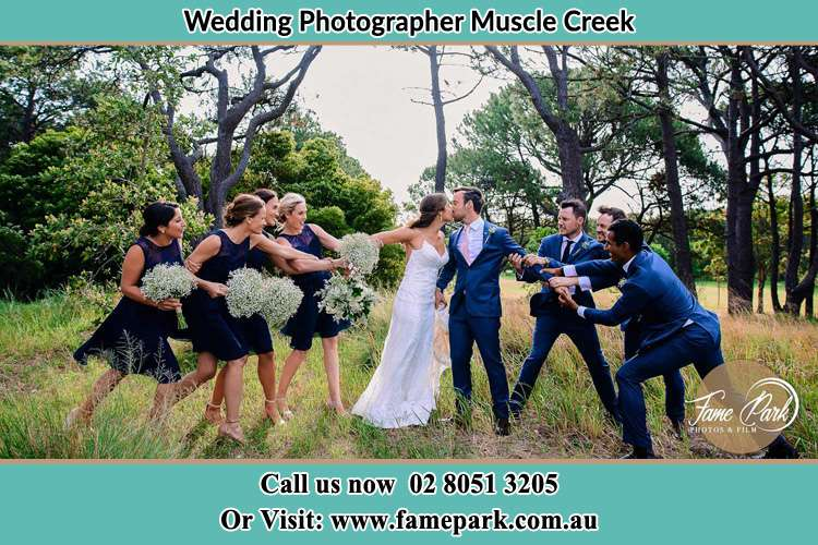 Photo of the Bride and the Groom kissing while teasing by the entourage Muscle Creek NSW 2333