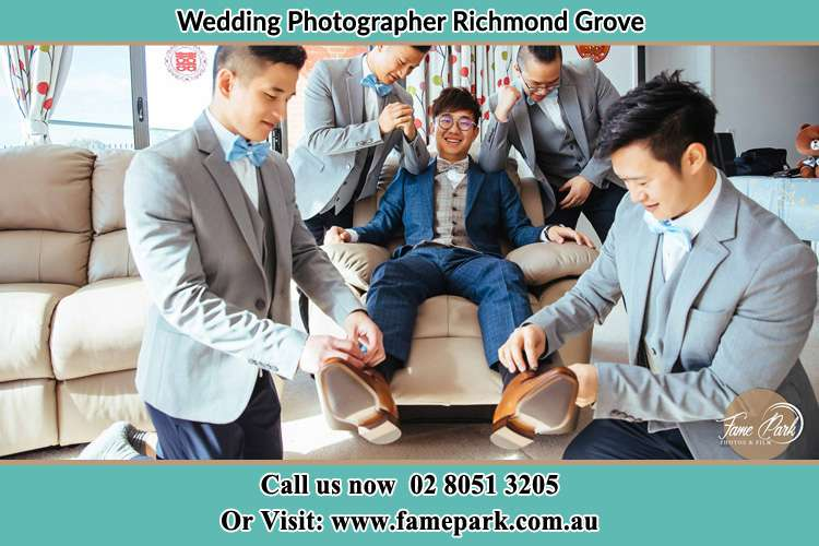 Photo of the Groom helping by the groomsmen getting ready Richmond Grove Rd NSW 2333