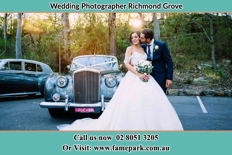 Photo of the Bride and the Groom at the front of the bridal car Richmond Grove Rd NSW 2333