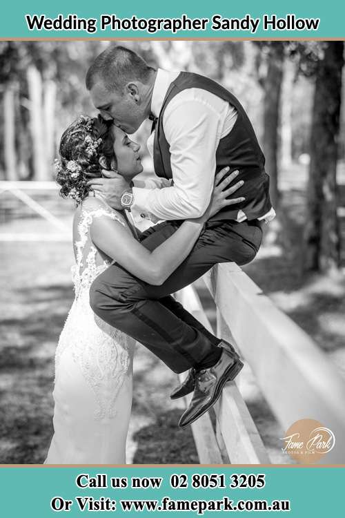 Photo of the Groom sitting on the fence while kissing the Bride on the forehead Sandy Hollow NSW 2333