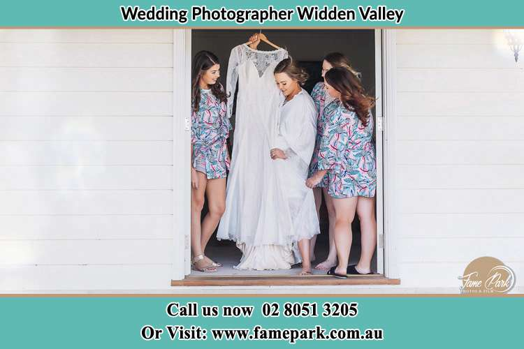 Photo of the Bride and the bridesmaids checking the wedding gown at the front door Widden Valley NSW 2328